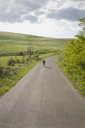 Cyclist on road through hills Stock Photo - Premium Royalty-Free, Code: 622-02198541