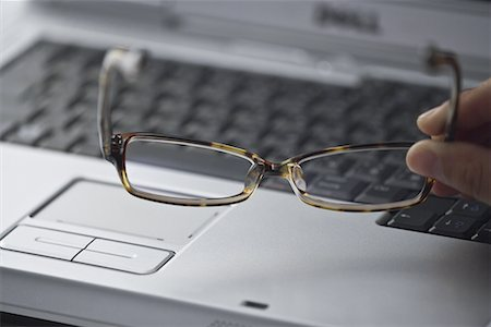 finger holding a key - Laptop computer and person holding spectacles Stock Photo - Premium Royalty-Free, Code: 622-02354368