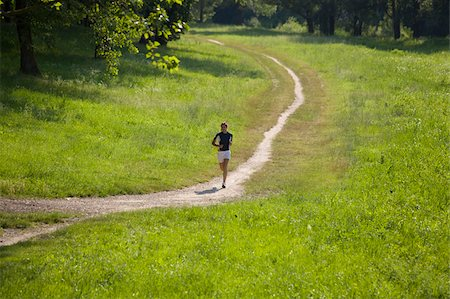 Teenage Girl Running on a Dirt Track Stock Photo - Premium Royalty-Free, Code: 622-02621572