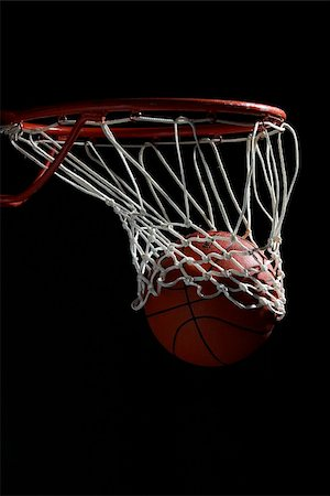 Basketball going through hoop against black background Stock Photo - Premium Royalty-Free, Code: 622-02913434
