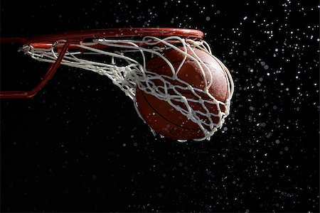 Basketball going through hoop Stock Photo - Premium Royalty-Free, Code: 622-02913431