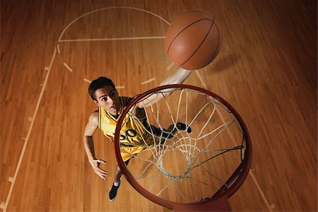 Young man throwing basketball in hoop Stock Photo - Premium Royalty-Free, Code: 622-02913433