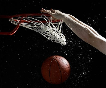 Hands of player slam dunking basketball into hoop Stock Photo - Premium Royalty-Free, Code: 622-02913445