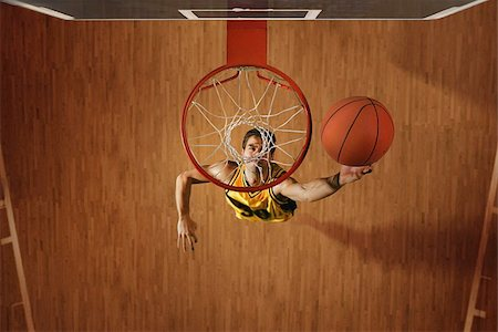 Basketball player slam dunking ball in hoop Stock Photo - Premium Royalty-Free, Code: 622-02913446