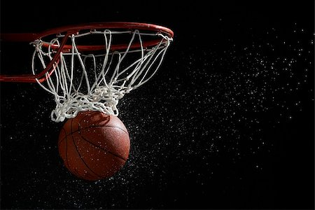 Basketball going through hoop against black background Stock Photo - Premium Royalty-Free, Code: 622-02913441