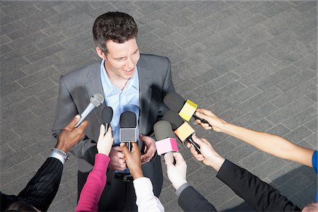Reporters holding microphones for politician Stock Photo - Premium Royalty-Free, Code: 635-05550033