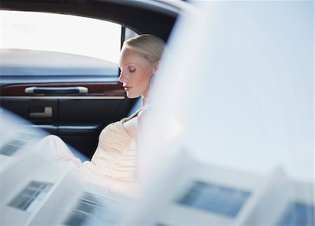 Woman sitting in backseat of limo Stock Photo - Premium Royalty-Free, Code: 635-05550057