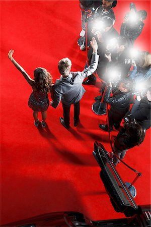 Celebrities waving to paparazzi on red carpet Stock Photo - Premium Royalty-Free, Code: 635-05550096
