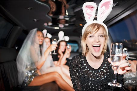 Woman in bunny ears drinking champagne in limo Stock Photo - Premium Royalty-Free, Code: 635-05550116