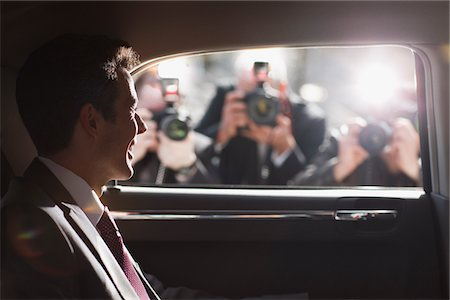 rich lifestyle - Politician smiling for paparazzi in backseat of car Stock Photo - Premium Royalty-Free, Code: 635-05550125