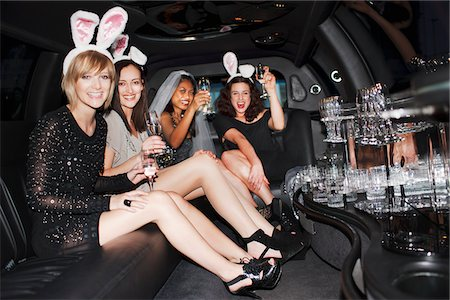 Women in bunny ears drinking champagne in limo Stock Photo - Premium Royalty-Free, Code: 635-05550132