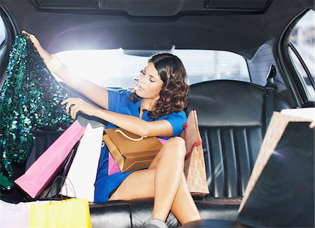 Woman with shopping bags in backseat of limo Stock Photo - Premium Royalty-Free, Code: 635-05550158