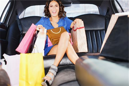 Woman with shopping bags in backseat of limo Stock Photo - Premium Royalty-Free, Code: 635-05550166