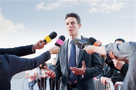 Politician talking into reporters' microphones Stock Photo - Premium Royalty-Free, Code: 635-05550160