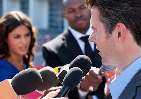 Politician talking into reporters' microphones Stock Photo - Premium Royalty-Free, Code: 635-05550163