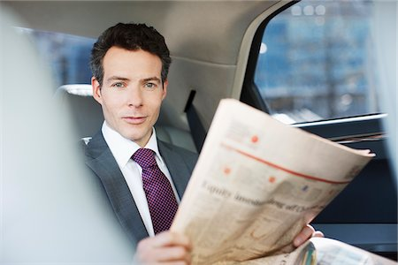 Politician reading newspaper in backseat of car Stock Photo - Premium Royalty-Free, Code: 635-05550174