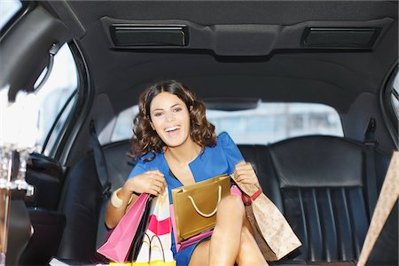 Woman with shopping bags in backseat of limo Stock Photo - Premium Royalty-Free, Code: 635-05550176