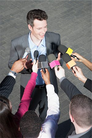 Politician talking into reporters' microphones Stock Photo - Premium Royalty-Free, Code: 635-05550186