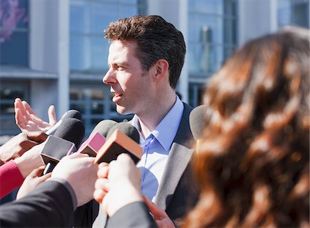 Politician talking into reporters' microphones Stock Photo - Premium Royalty-Free, Code: 635-05550183