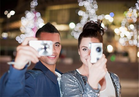 Couple taking pictures on city street at night Stock Photo - Premium Royalty-Free, Code: 635-05550190