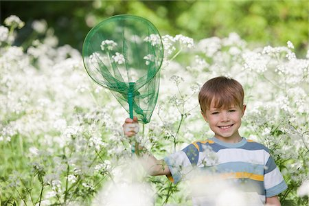 Boy playing with butterfly net in field of flowers Stock Photo - Premium Royalty-Free, Code: 635-05550224