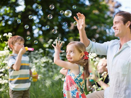 Family playing with bubbles in park Stock Photo - Premium Royalty-Free, Code: 635-05550235