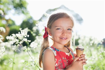 Girl eating ice cream outdoors Stock Photo - Premium Royalty-Free, Code: 635-05550237