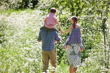 Parents carrying children on their shoulders outdoors Stock Photo - Premium Royalty-Free, Code: 635-05550258