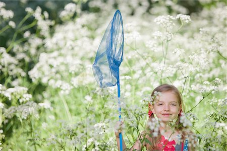 Girl playing with butterfly net in field of flowers Stock Photo - Premium Royalty-Free, Code: 635-05550252