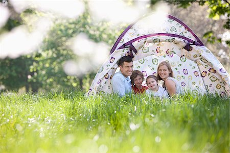 Family sitting in tent in park Stock Photo - Premium Royalty-Free, Code: 635-05550260