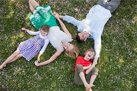 Family laying in grass together Stock Photo - Premium Royalty-Free, Code: 635-05550261