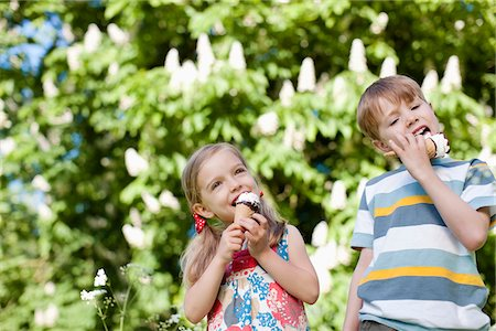 Children licking ice cream outdoors Stock Photo - Premium Royalty-Free, Code: 635-05550270