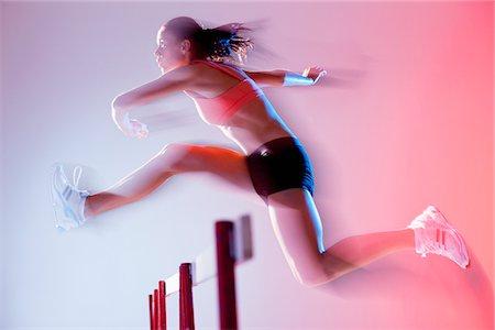 Blurred view of runner jumping hurdles Stock Photo - Premium Royalty-Free, Code: 635-05550494