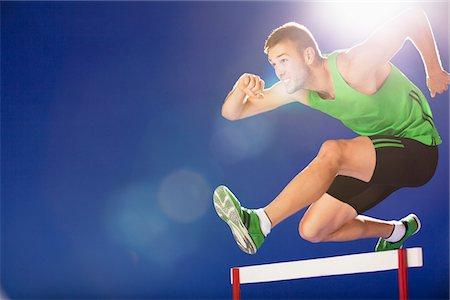 Athlete jumping hurdles Stock Photo - Premium Royalty-Free, Code: 635-05550533