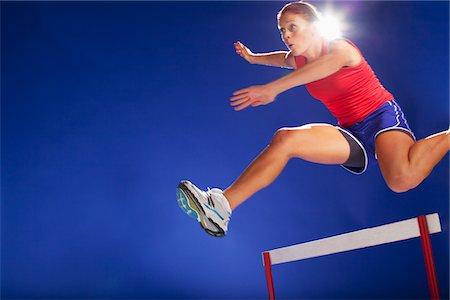 Athlete jumping over hurdles Stock Photo - Premium Royalty-Free, Code: 635-05550564