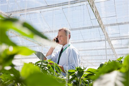 Businessman talking on cell phone in greenhouse Stock Photo - Premium Royalty-Free, Code: 635-05550688