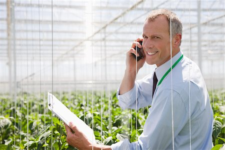 Businessman talking on cell phone in greenhouse Stock Photo - Premium Royalty-Free, Code: 635-05550712