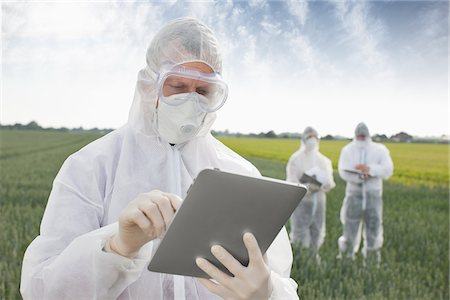 Scientist in protective gear using tablet computer Stock Photo - Premium Royalty-Free, Code: 635-05550734