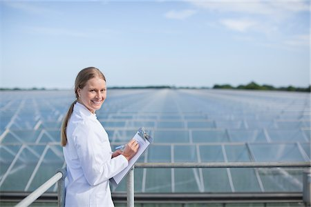 Scientist examining roofs of greenhouses Stock Photo - Premium Royalty-Free, Code: 635-05550739