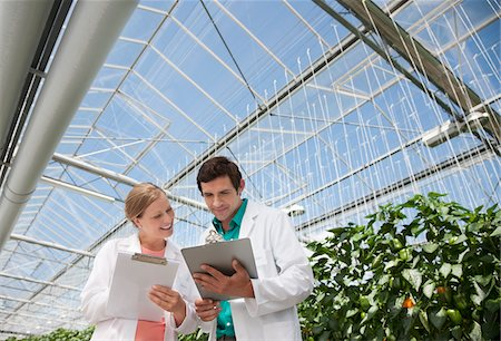 Scientists writing on clipboards in greenhouse Stock Photo - Premium Royalty-Free, Code: 635-05550764