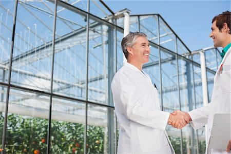 production - Scientists shaking hands outside greenhouse Stock Photo - Premium Royalty-Free, Code: 635-05550774