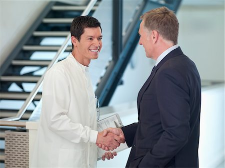 Businessman shaking hands with scientist Stock Photo - Premium Royalty-Free, Code: 635-05550825