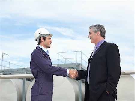 Worker and businessman shaking hands outdoors Stock Photo - Premium Royalty-Free, Code: 635-05550926
