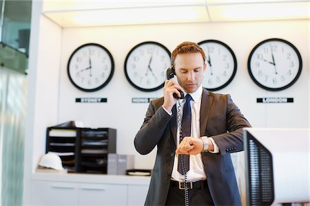 Businessman checking his watch in office Stock Photo - Premium Royalty-Free, Code: 635-05551066