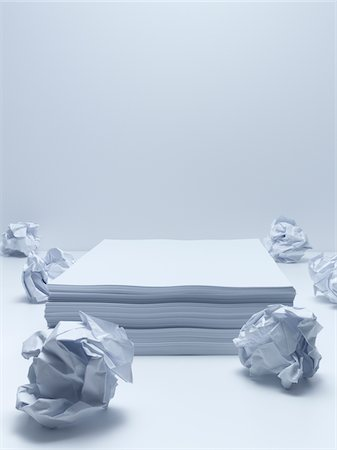 Crumpled balls of paper with stack of paper Stock Photo - Premium Royalty-Free, Code: 635-05551077