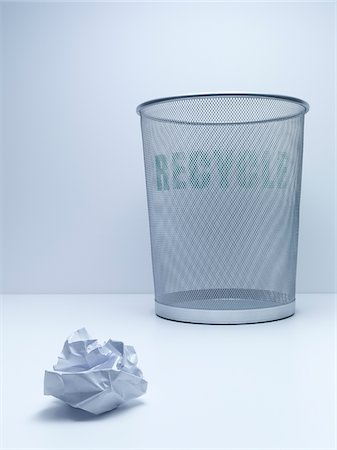 Crumpled ball of paper beside recycling bin Stock Photo - Premium Royalty-Free, Code: 635-05551090