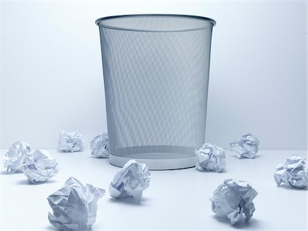 Crumpled balls of paper beside wastebasket Stock Photo - Premium Royalty-Free, Code: 635-05551092