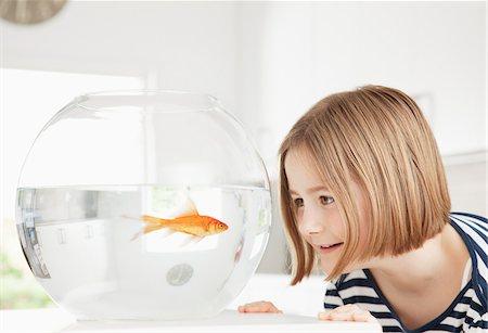 preteen swim - Girl examining goldfish in fishbowl Stock Photo - Premium Royalty-Free, Code: 635-05551104