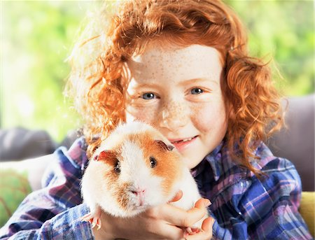Girl holding pet hamster in living room Stock Photo - Premium Royalty-Free, Code: 635-05551106