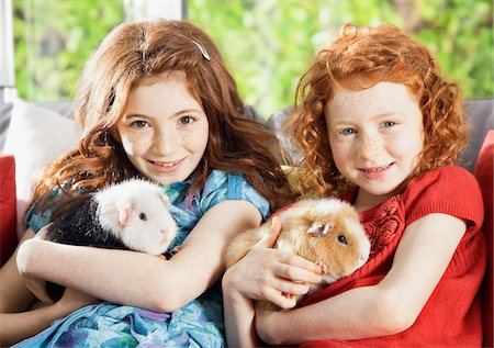 red hair preteen girl - Girls holding pet hamsters in living room Stock Photo - Premium Royalty-Free, Code: 635-05551114